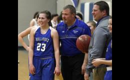 Emily Beseman (L) was surprised to pass the milestone on Friday, and celebrated with her dad, assistant coach Tom Beseman (M), and head coach Aaron Gapinski (R).