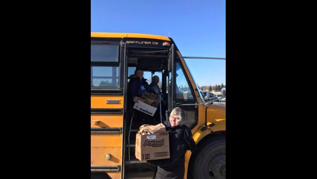 Staff from the Long Prairie-Grey Eagle School District prepare a delivery to students via bus.