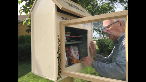 Chuck McMurray of Long Prairie shows off his free library located in his front yard. Book lovers are encouraged to come to the Little Free Library and take a book or share a book.