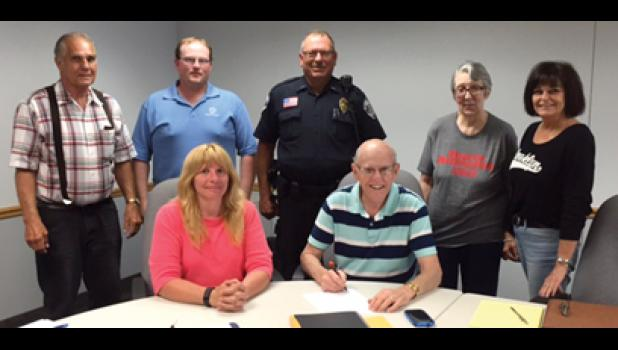 "Mayor Don Rasmussen signs a proclamation declaring Tuesday, August 4, 2015 as ""National Night Out"" in the city of Long Prairie. On hand for the signing of the proclamation were, in back, from left, council members Tony Towle, Devin Hines, police chief and NNO co-chair Kevin Langer, council member Lila Gripne, Hands of Hope General Crime Coordinator and NNO co-chair Barb Dinkel Goodrich. In front, Long Prairie City Administrator Brenda Thomes and Mayor Don Rasmussen. Not pictured: council member Art Rowan."