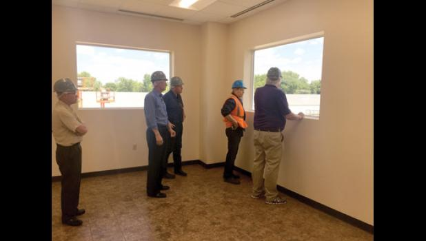 Vice President of Operations at Long Prairie Packing Kevin Fairchild, in the vest, explains how expansion will affect production from the newly constructed office building to Senator Paul Gazelka and Tom Rosen.