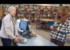 Long Prairie librarian Nancy Potter helps a library member check out items. The library offers many more services than just books and DVDs.