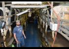 Jeff Rinde in the eight stall milking parlor along with one of the farm's employees who is milking the cows. The parlor makes milking the 250-cow herd more manageable.